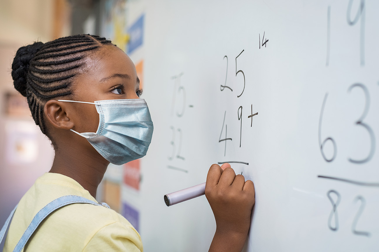 Elementary girl wearing mask at school